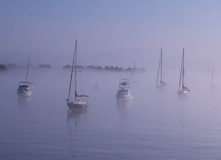 Sailboats are seen on dark water in Salem Harbor as fog gives a gloomy, gray shadow to the morning