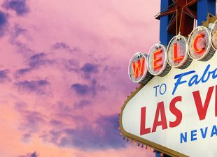 The iconic welcome sign in Las Vegas is illuminated in front of a pink and purple sky on a gorgeous summer sunset