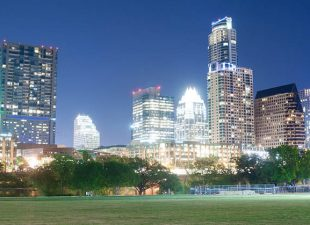 The bright lights of the downtown skyline of Austin, Texas are pictured at dusk behind a green field in Zilker Park.