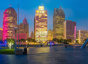 View of the riverfront walk in downtown Detroit, Michigan with the skyline and walkway illuminated on a clear night in summer.