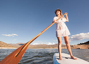 A woman smiles as she stands tall on a stand-up paddleboard on calm water while holding a wooden paddle and looking into the distance on a clear, sunny day.