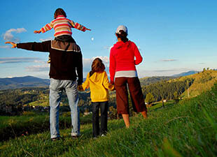 A family of four soaks in the views of mountains in the distance after hiking up a green hill on a bright summer evening.