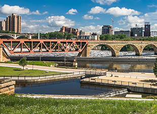 Panoramic view of stone arch bridge crossing the Mississippi River on a sunny day in Minneapolis