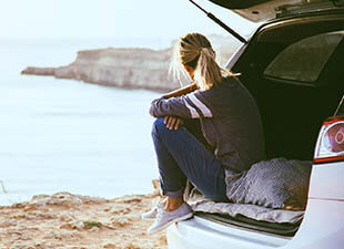 A college-aged woman relaxes on the rear of her car, gazing out at a body of water behind her during daytime