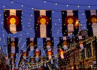 Rows of Colorado flags hang vertically with many strands of illuminated string lights across a street in Larimer Square in Denver at dusk