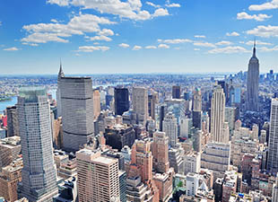 A aerial view of the New York City, Manhattan midtown skyline with a bright blue sky and white puffy clouds in the background on a clear day