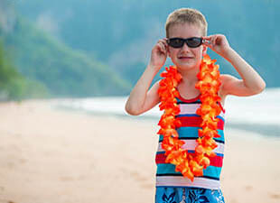 Young boy wearing an orange and yellow lei over a striped red and blue tank top and dark sunglasses during the day on a beach in Honolulu Hawaii