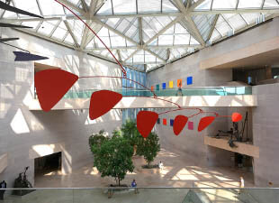 Colorful art is suspended over trees in the atrium of the National Gallery East Building with a glass ceiling in Washington, D.C. on a bright afternoon
