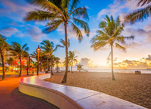 The sky is blue and golden yellow as the sun rises over Fort Lauderdale beach and surrounding palm trees on a summer morning.