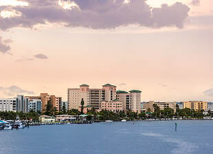 Bright blue waters from the ocean are pictured in the foreground in front of the Fort Myers, Florida skyline, with a beautiful pink sunset sky in the background in the evening