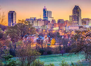 Trees and a river are pictured in front of the illuminated skyline view of Raleigh, North Carolina during a purple and orange hued sunset