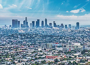 View of the downtown Los Angeles skyline with sprawling residential neighborhoods reaching far into the distance on a beautiful, sunny day.