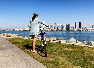 A woman wearing a baseball hat and sweater with shorts stands next to her bike in the grass along San Diego's shoreline looking at the city's skyline