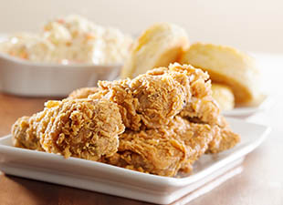 A plate of fried chicken is ready to be enjoyed at Fodder & Shine in Tampa, Florida with biscuits and side dishes in the background.
