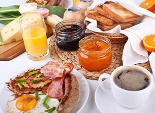 Coffee, an egg and ham breakfast, orange juice, jellies and toast sit on a table with a white tablecloth at a restaurant in Minneapolis, Minnesota
