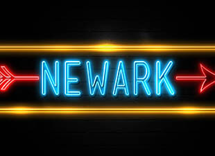 illuminated against a black background is a neon yellow, red and blue Newark sign with arrow pointing