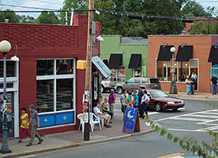 View of street corner in NoDa neighborhood in Charlotte, North Carolina with patrons waiting outside of colorfully painted shops and restaurants on a bright day