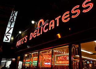 A red neon sign reading, Katz's Delicatessen lights up the night sky in New York City above the illuminated windows for Katz's Delicatessen in the Lower East Side with more neon signs