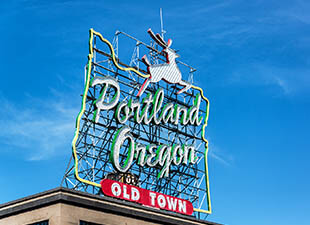 """A large outdoor sign reading: """"Portland Oregon Old Town"""" in the outline of Oregon State with a deer jumping over it, under blue sky"""