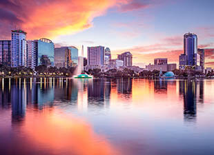 The downtown skyline of Orlando, Florida is illuminated by an orange and pink sky at sunset on a warm summer evening.