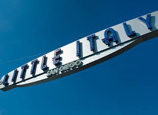 San Diego's Little Italy sign with blue lettering and white background under blue sky