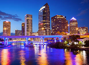 The Tampa, Florida skyline is illuminated, while the bridge in the foreground is lit up a bright blue, reflected over Tampa Bay at sunset in front of clear sky with a few clouds