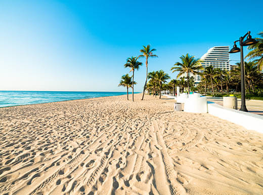 A view down Fort Lauderdale Beach  with palm trees and white sand with footprint tracks under blue sky on the edge of turqoise water.