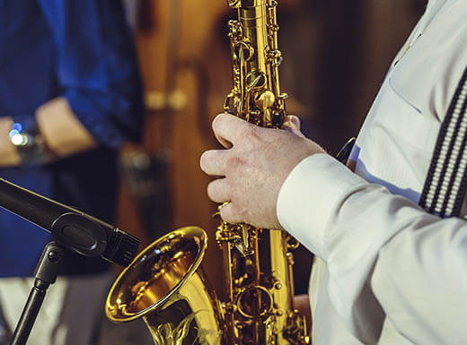 A close-up of a man in a white shirt with black and white striped suspenders playing the saxophone during a live performance at Blues City Deli in St. Louis, Missouri on a busy evening.