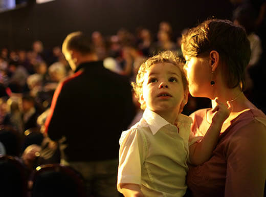 A young boy watches a concert performance while sitting on his mom's lap on a warm evening.