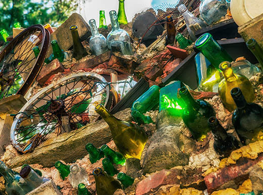 Outdoor mixed-media art installation featuring green and brown bottles and bicycle wheels at Magic Gardens in Philadelphia