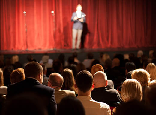 A stand-up comedian stands in front of a red curtain on a stage in front of an audience of people in Fort Myers, Florida