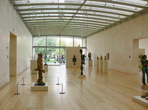 Interior of Nasher Sculpture Center in Dallas, Texas shows numerous dark sculptures in a light room with a glass ceiling and large window.