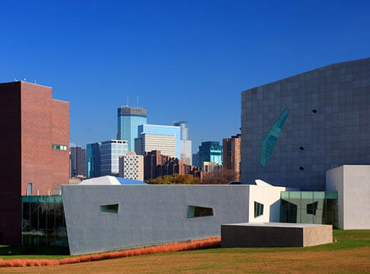 View of the Walker Art Center building in downtown Minneapolis, surrounded by other buildings in the city, on a clear sunny day