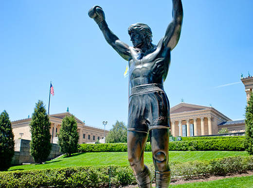 Iconic Rocky Balboa statue glistening in the morning sun just outside of the Philadelphia Museum of Art.