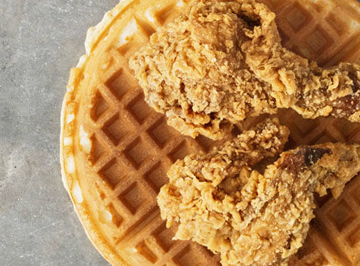 Two pieces of crispy fried chicken sit atop a golden brown and round waffle served atop a grey countertop.