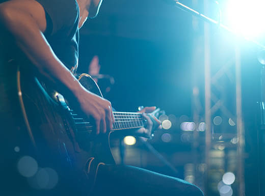 The side view of a male musician playing guitar on stage at night during the SXSW music festival is pictured to the left, with a bright white spotlight shining on the right in Austin, Texas