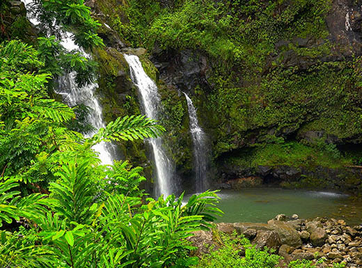 Upper Waikani Falls through bright greenery during the day in Maui Hawaii