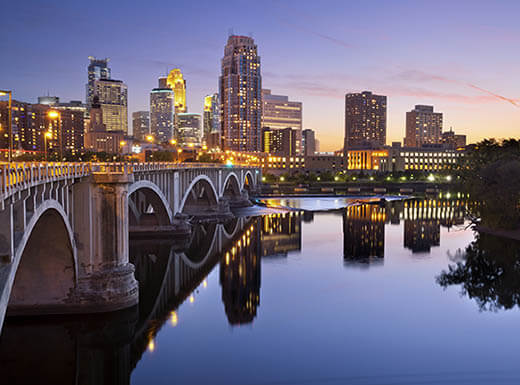 The Stone Arch Bridge is pictured in the foreground, reflected against still waters of the Mississippi River with the city of Minneapolis, Minnesota illuminated in the background against a sky at sunset