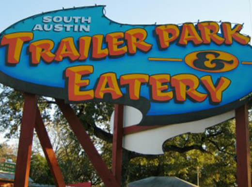 A blue and orange sign sits beneath the evening sky outside of South Austin Trailer Park & Eatery in Austin, Texas.