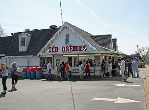 The exterior of Ted Drewes, a white house near the road, is pictured with people lined up for delicious and affordable desserts in St. Louis, Missouri at lunchtime on a summer day.