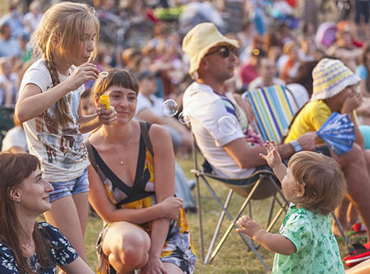 A mother watches while her two young children smile and play with bubbles while sitting outdoors on the grass during an early evening concert