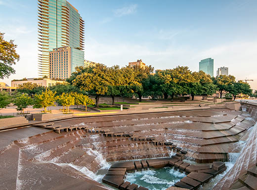 View of the Fort Worth Texas water gardens shows water cascading down terraces that lead to a pool with the Forth Worth downtown seen close behind, a local favorite spot