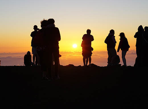Silhouettes of people watching the sunset on Maui