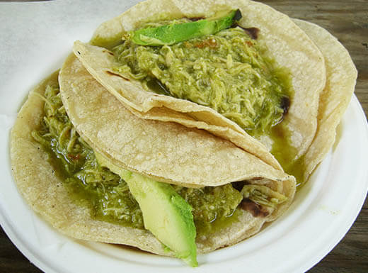 Moist shredded chicken tacos topped with fresh avocado slices sit atop a plate on a picnic table outside of El Naranjo Food Truck in Austin, Texas.