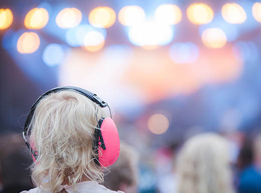 A young child wears pink ear protectors at a concert with stage lights seen in the distance on a spring evening.