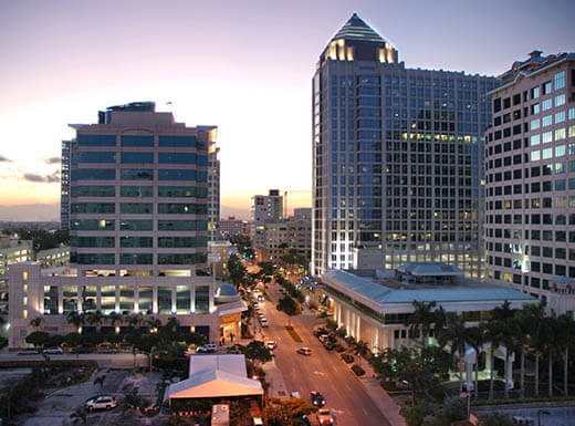 Downtown view of Fort Lauderdale skyscrapers high above the busy city streets, illuminated at dusk