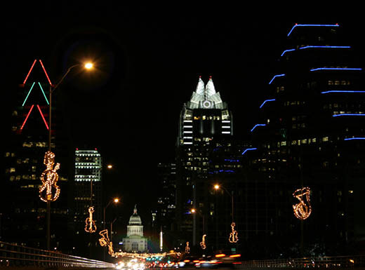 Blue, red, green and white lights illuminated on buildings are pictured against a black night time sky in Austin, Texas