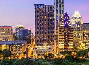 The bright night skyline of Austin, Texas pictured illuminated at dusk, reflected in Lady Bird Lake.