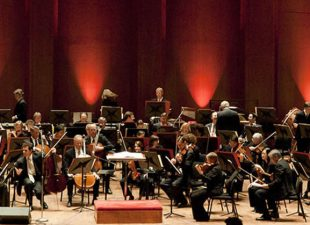 A view of the Houston Symphony on stage in front of an uplit red curtain preparing for performance in Houston, Texas