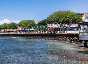 A row of waterfront restaurants are on the edge of the shore on Maui's West Shore looking out over a beautiful view of both Lanai and Molokai Islands on a sunny day
